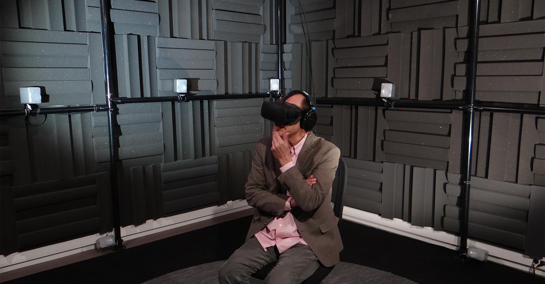 Man sitting in a room, wearing virtual headset, pink shirt being worn