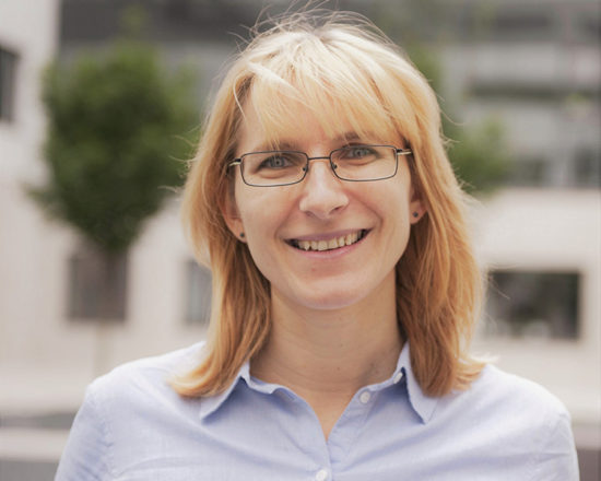 blonde woman with spectacles smiling at camera