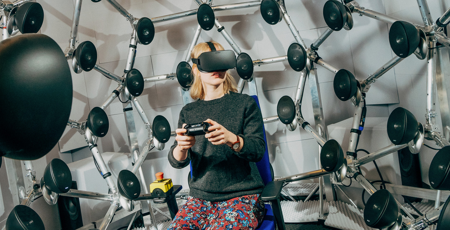 Lady sitting with a virtual headset on and holding a controller surrounded by speakers
