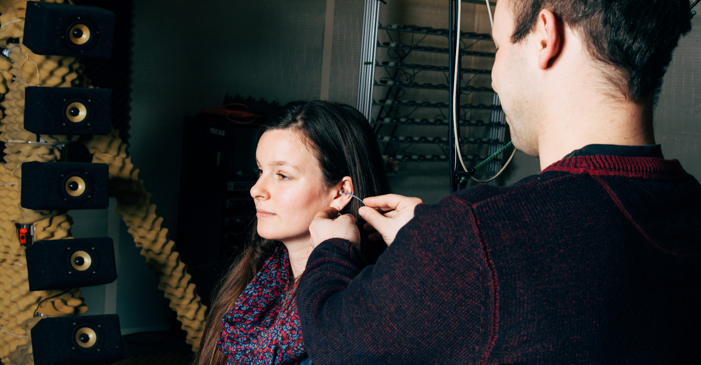 two people in image with one person inspecting the other's ear