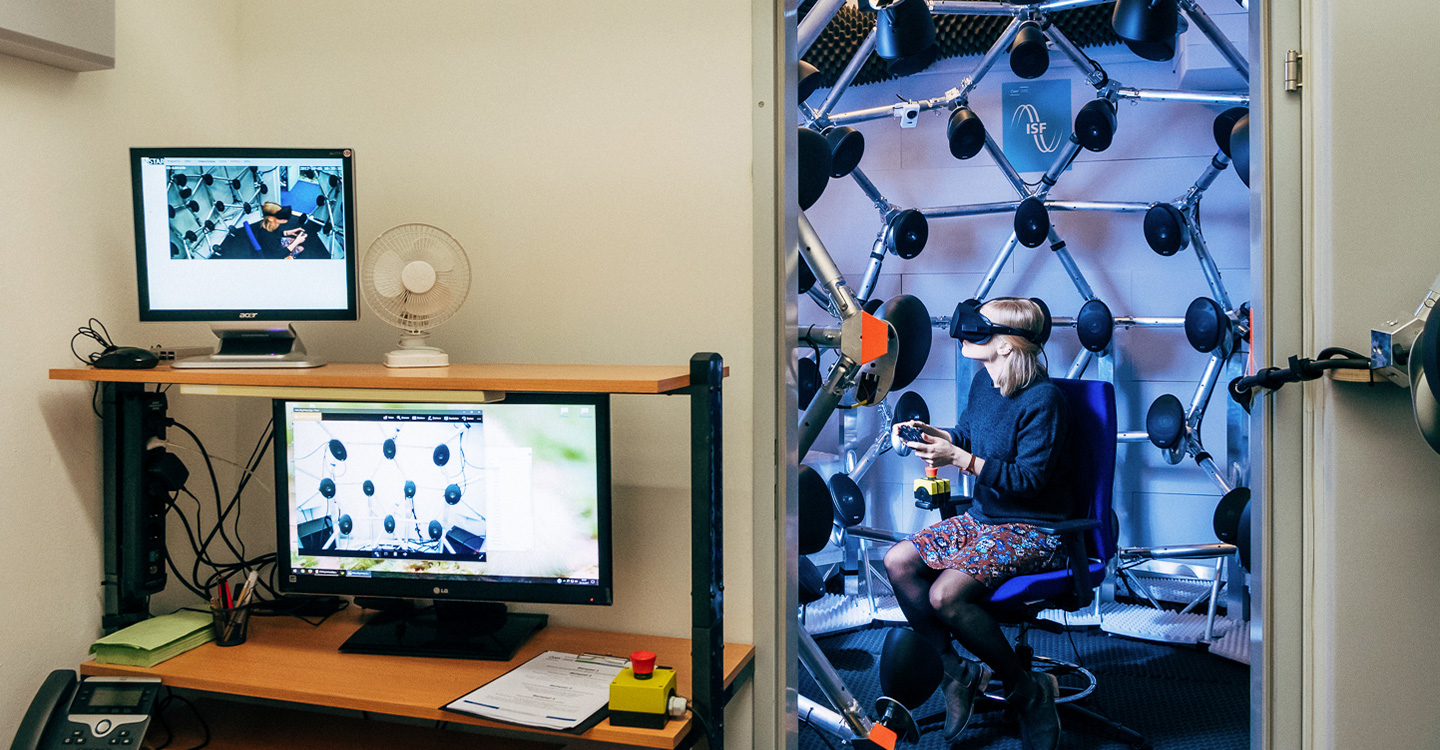 two rooms with computers in the first and a person in the second wearing a virtual headset and surrounded by speakers
