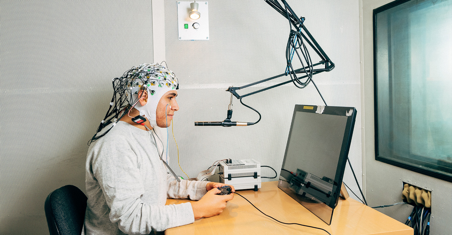 Person wearing cap with sensors on it looking at a computer screen