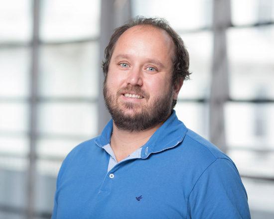 man in blue shirt smiling at camera