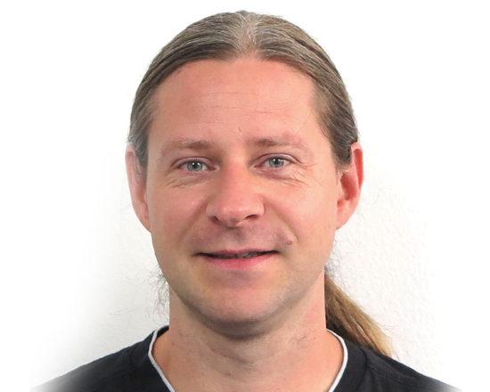 man in black shirt smiling at camera